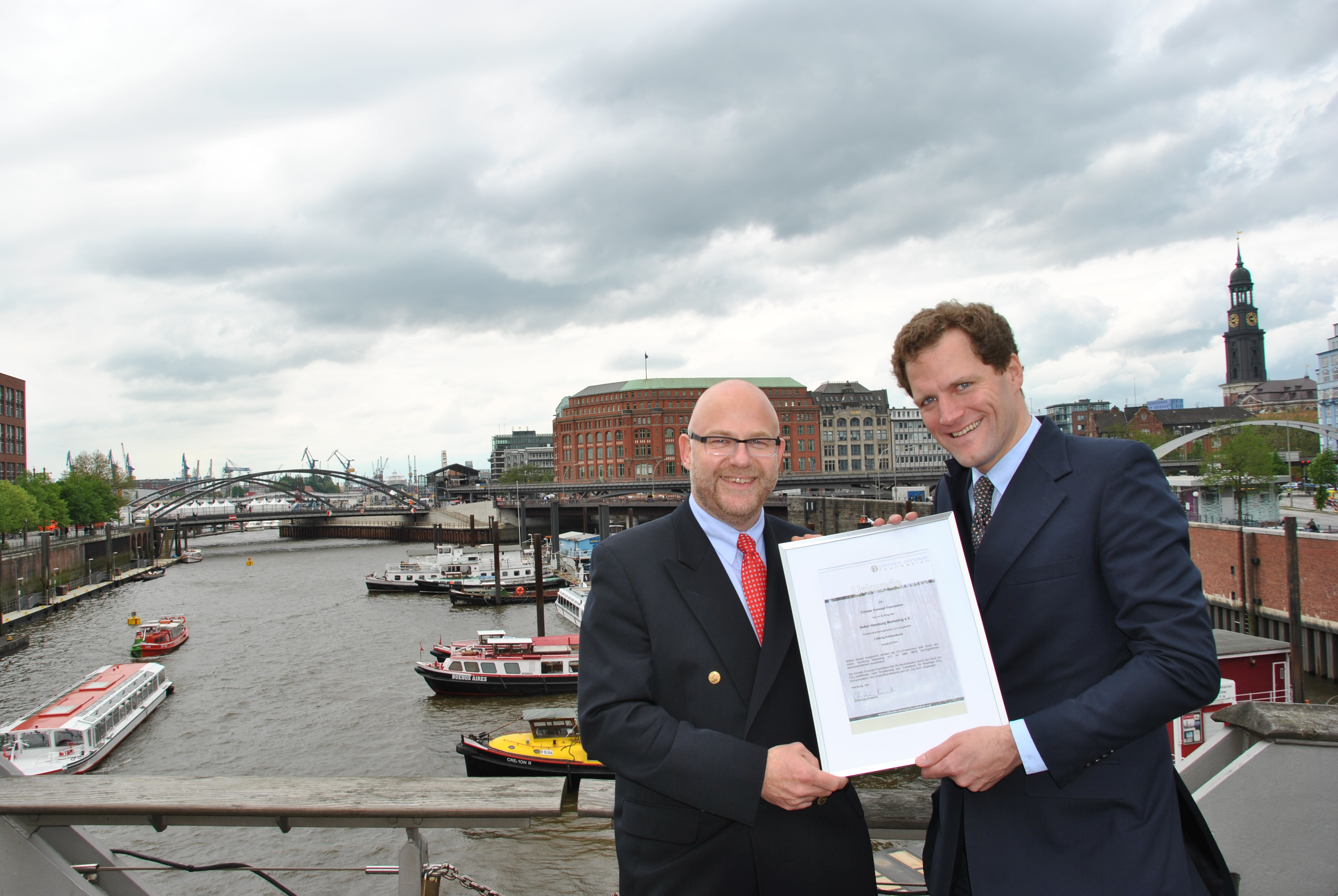 CCF Excutive Director Christopher Brandt (right) hands over the official document that confirms the CO2-neutralization to the Excutive Director of Port Hamburg Marketing, Axel Mattern
